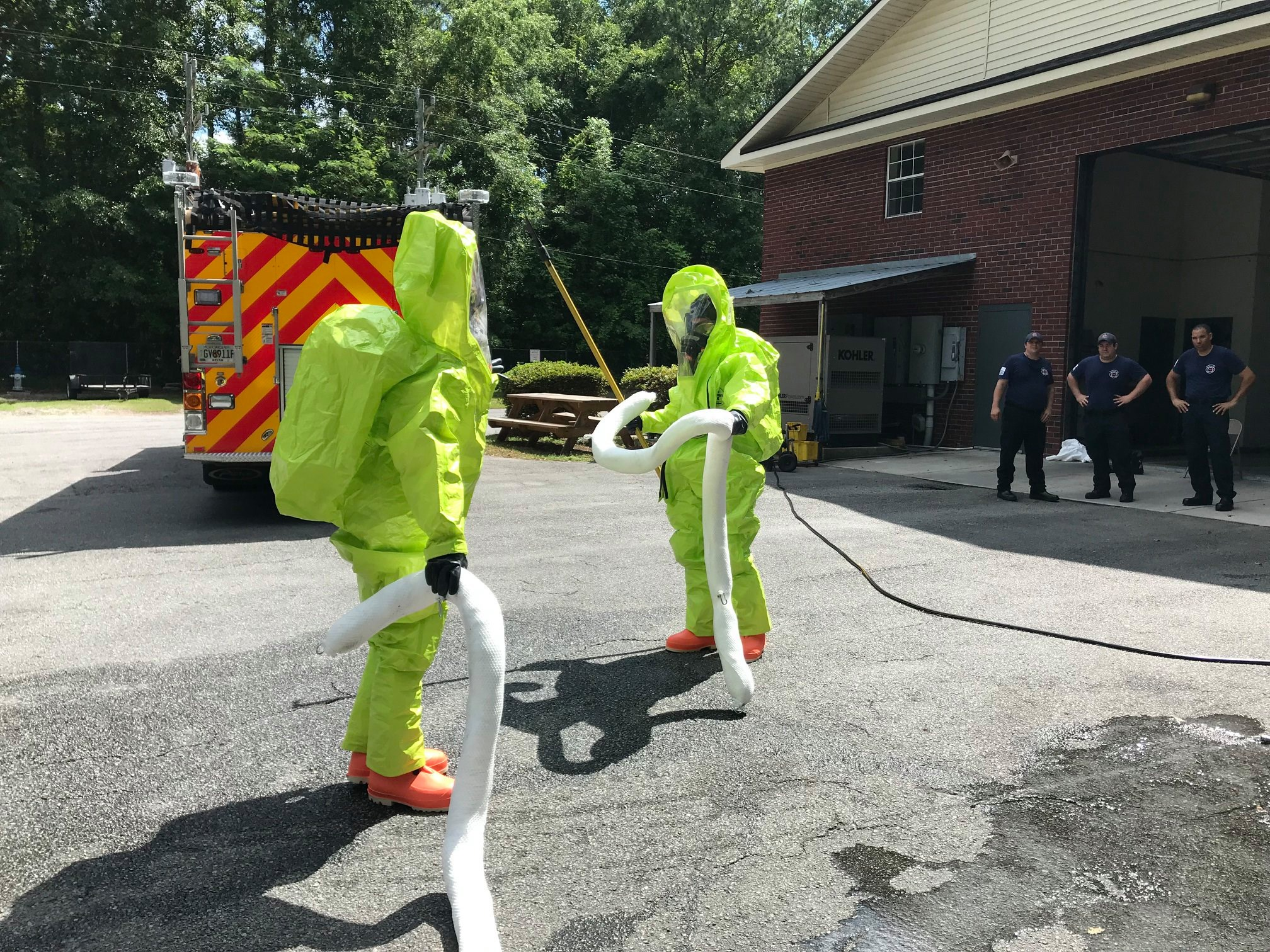 Two firefighters in hazmat suits holding a white tube