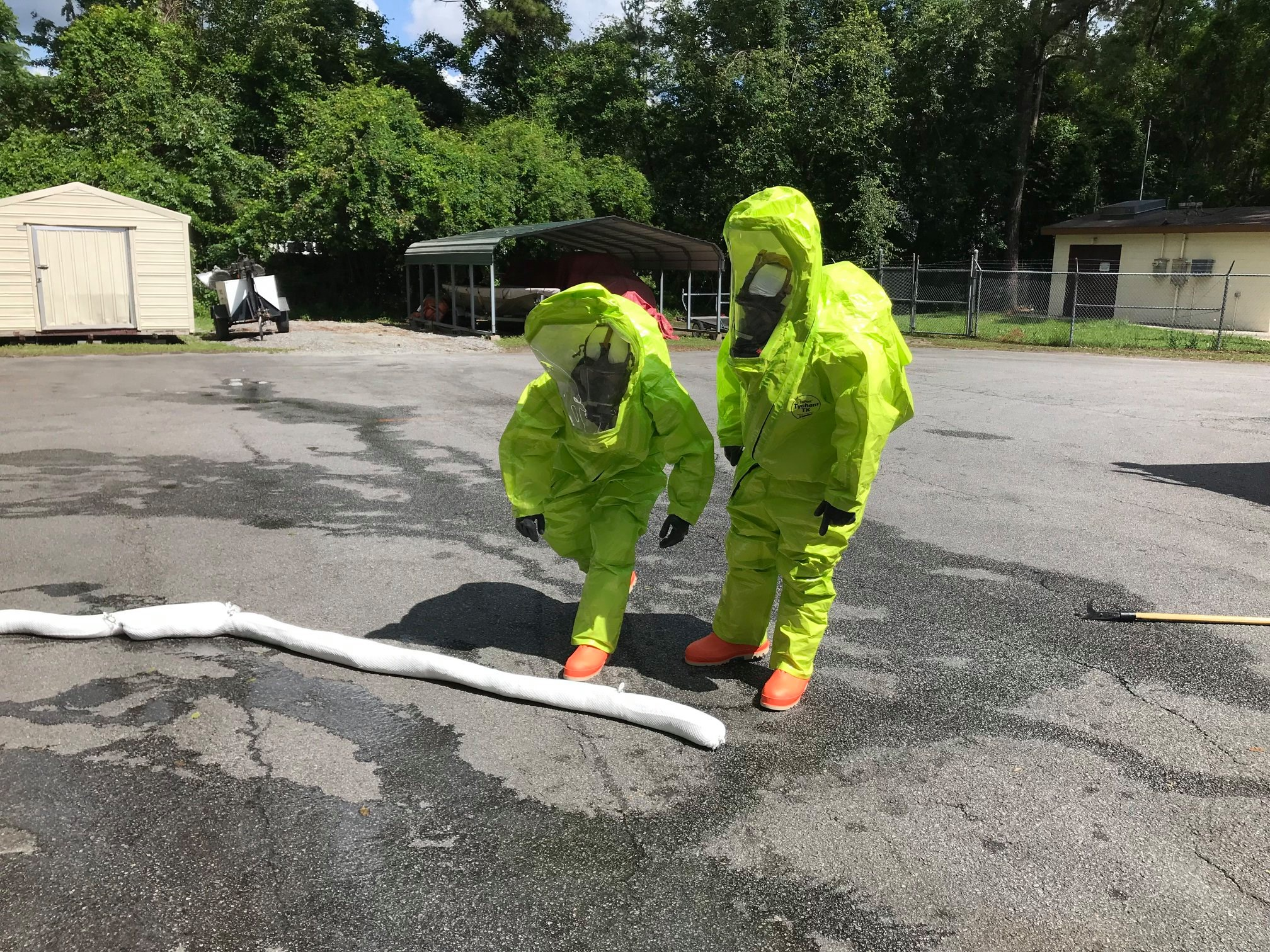 Two firefighters in hazmat suits laying out a white pipe