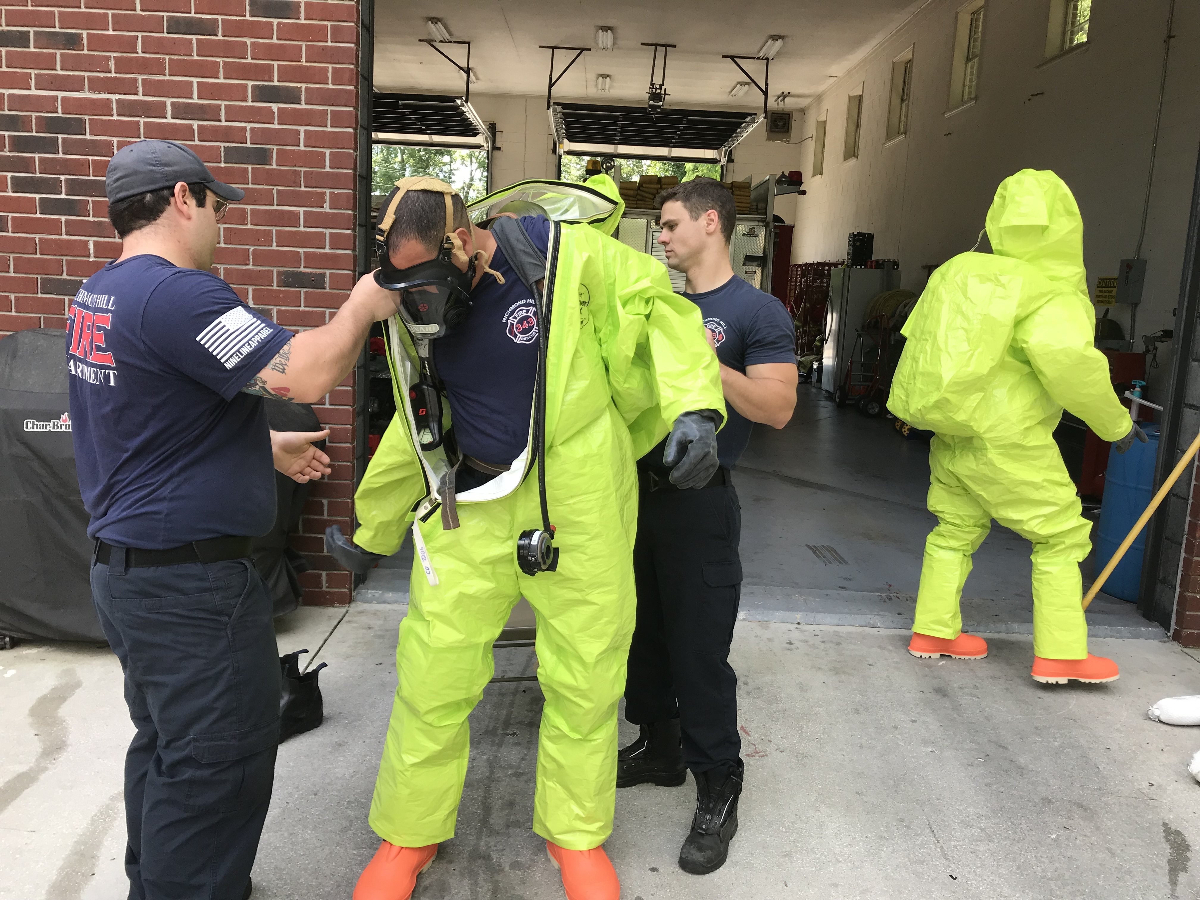 A firefighter being put into a Hazmat suit