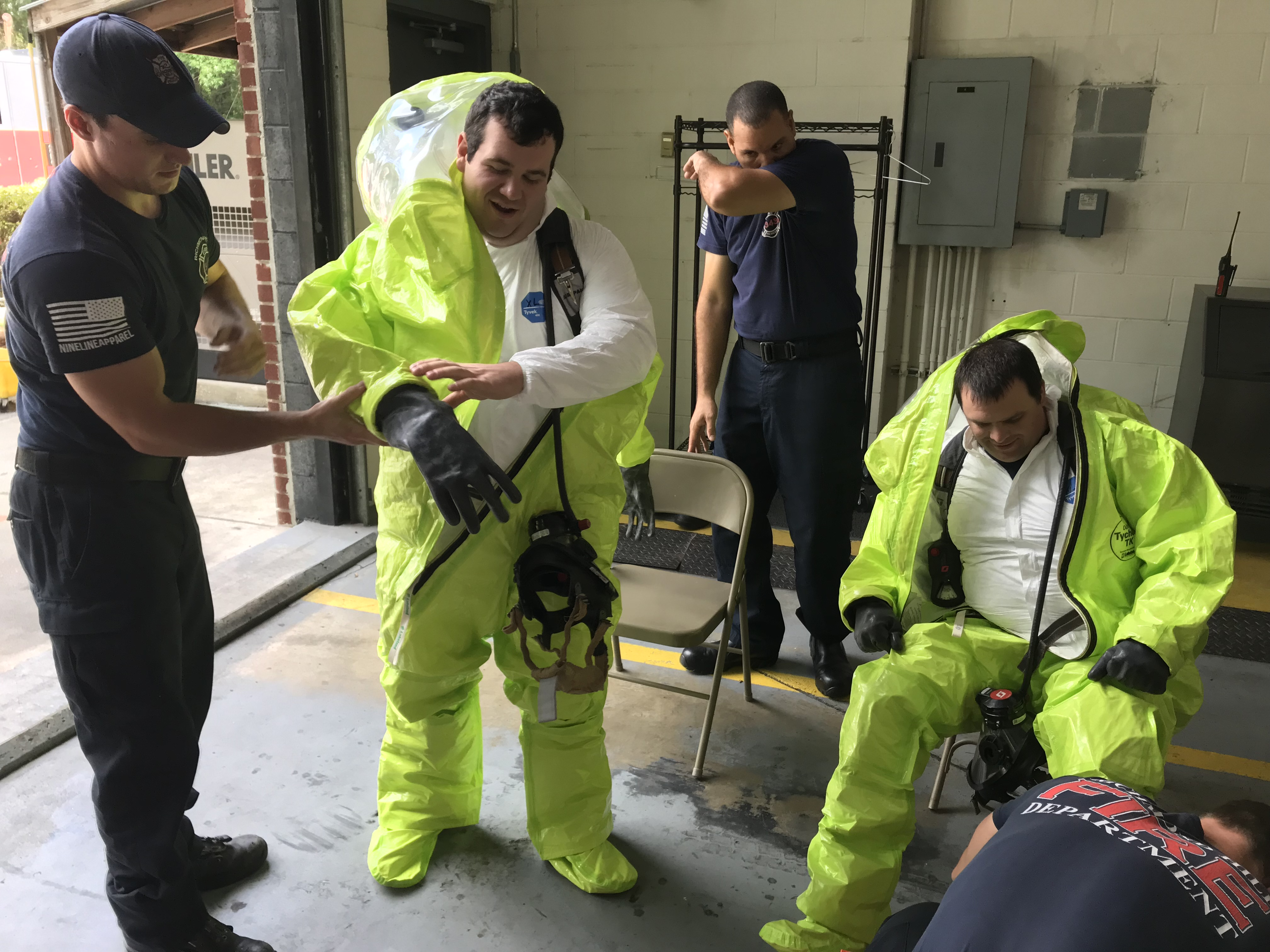 Two firefighters putting on hazmat suits