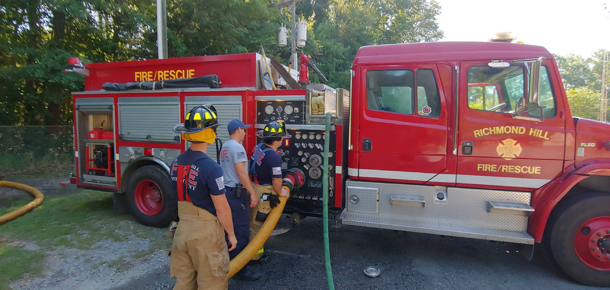 Three firefighters attaching a hose to a fire truck