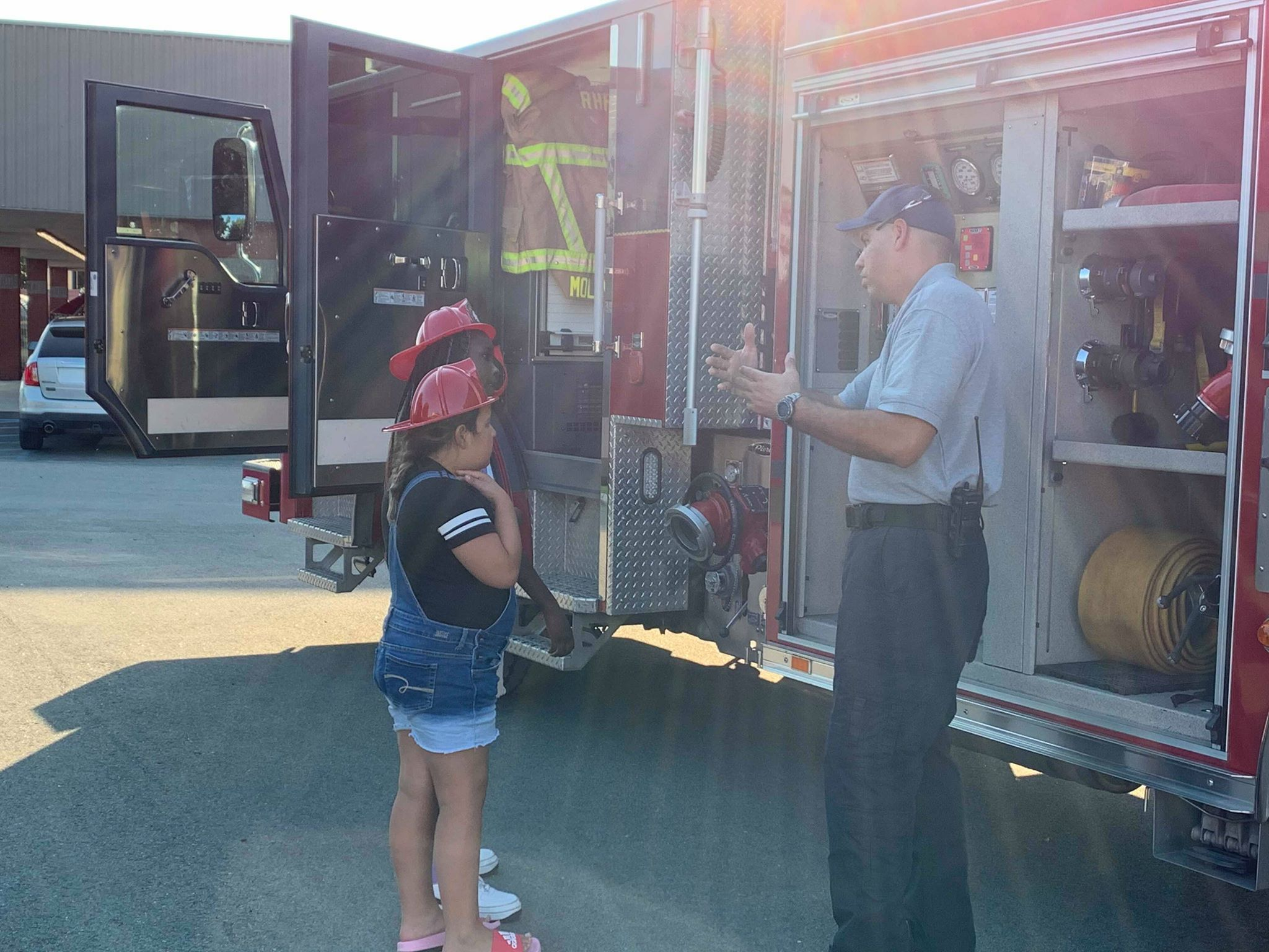 A man standing next to a firefighter talks to two kids