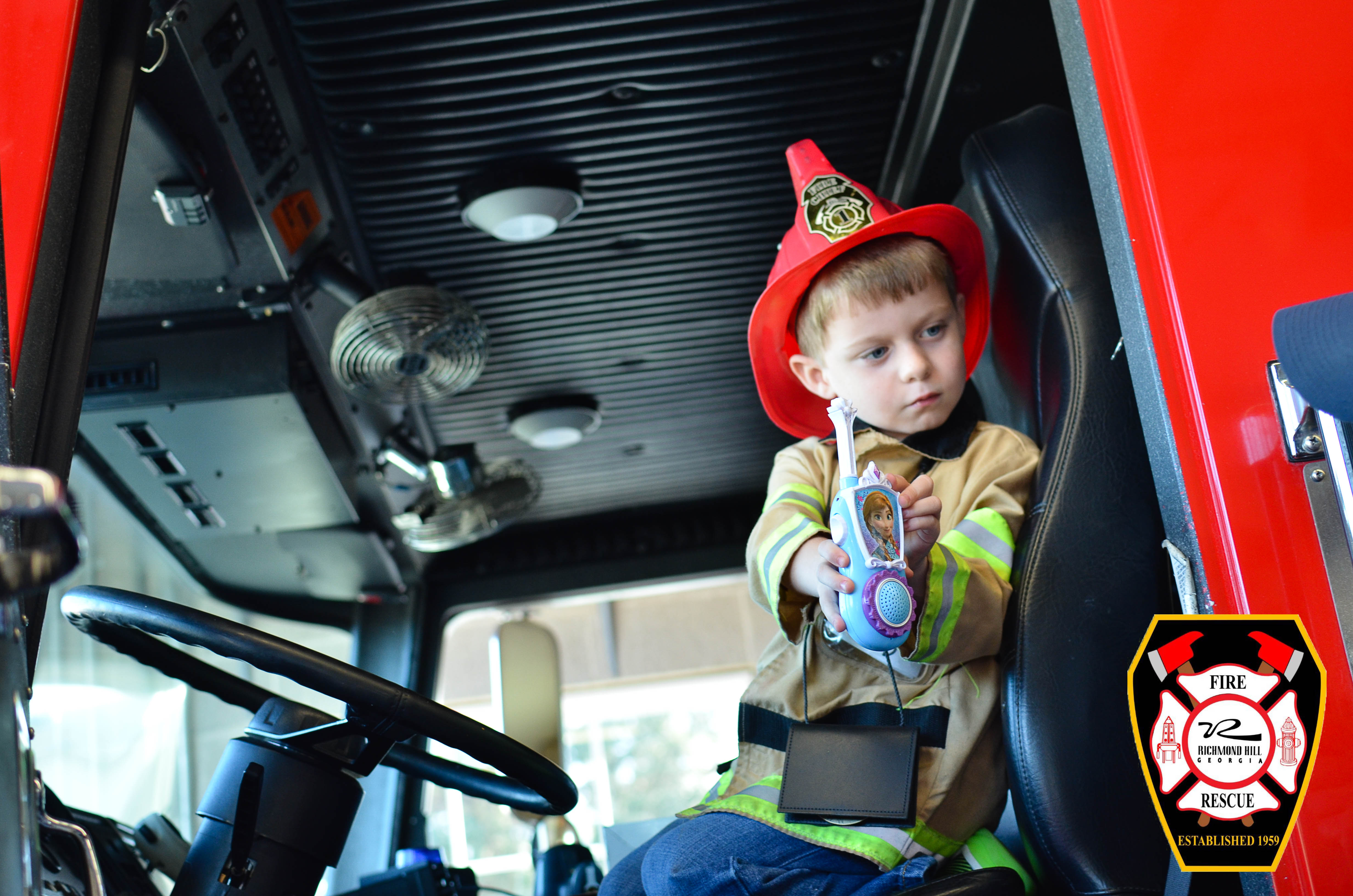 A young child sits in a fire truck