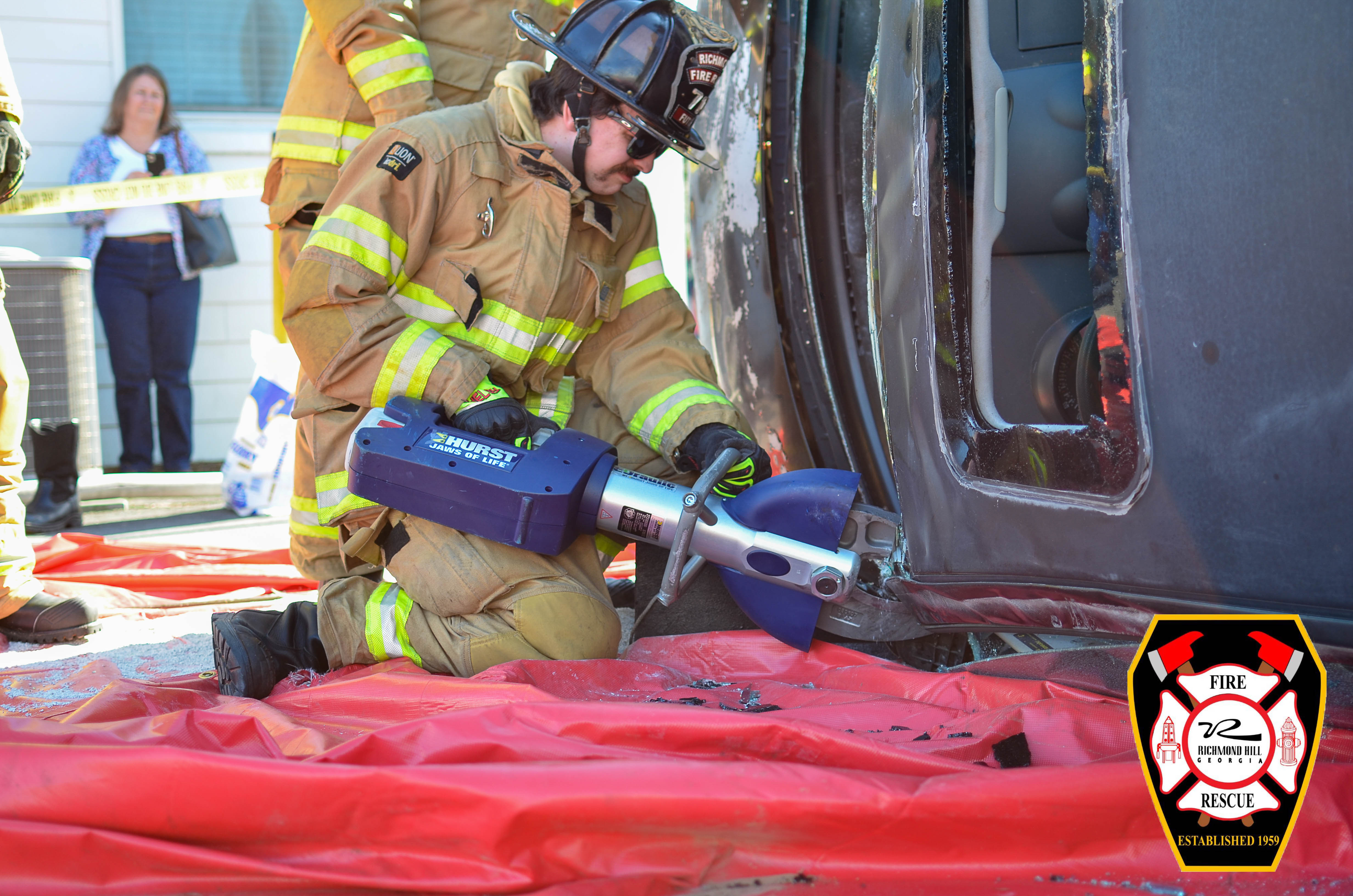 A firefighter uses a took to cut open a wrecked car