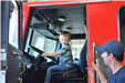 young boy sitting in driver's seat of fire truck