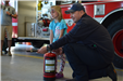 firefighter demonstrates use of fire extinguisher