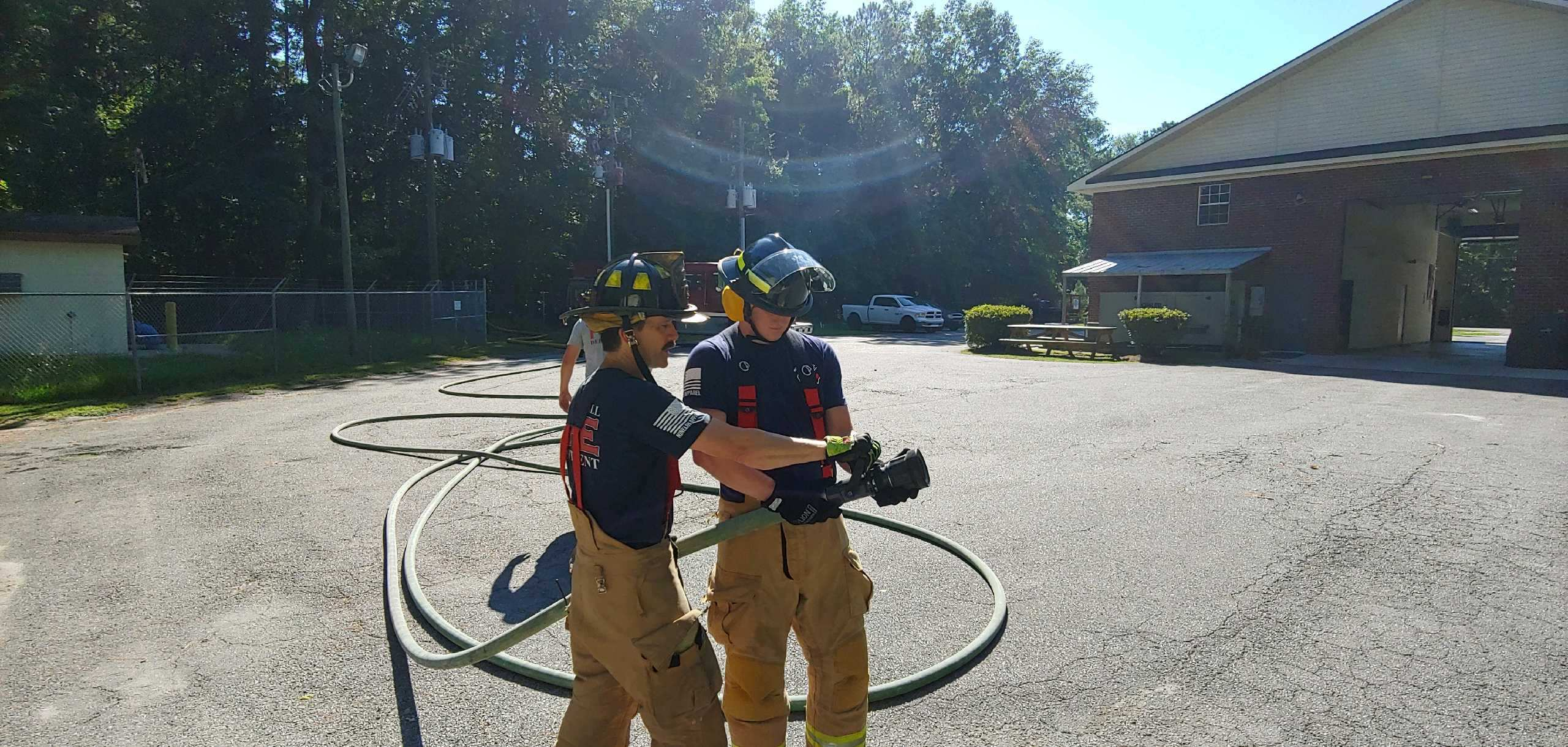 Two firefighters looking at a hose