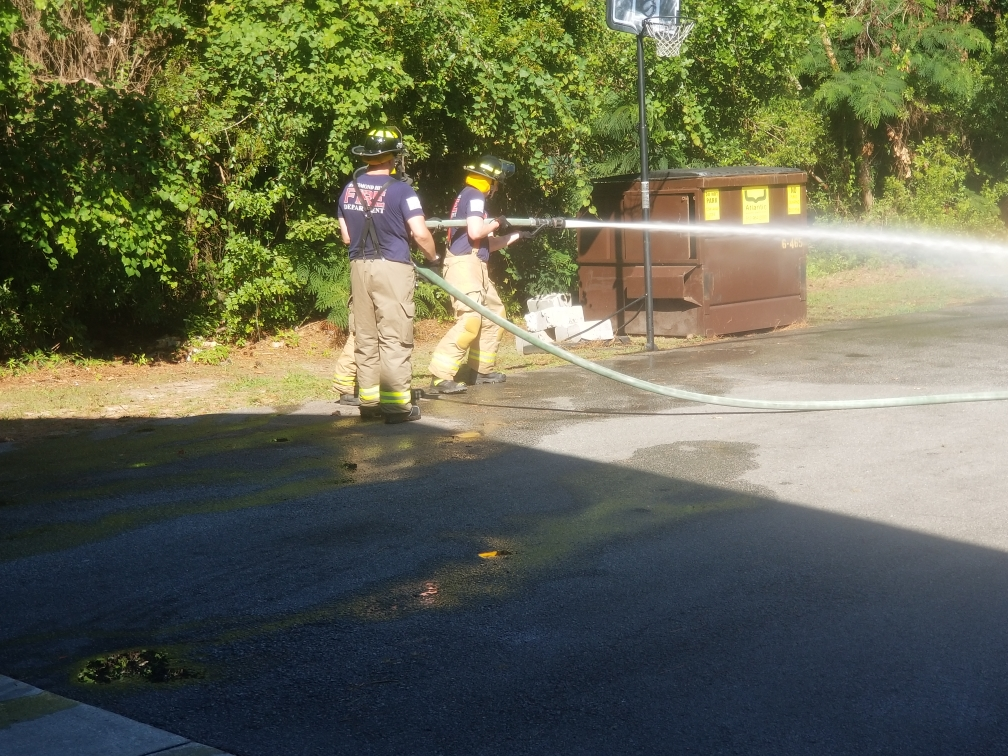 Firefighters spraying a parking lot