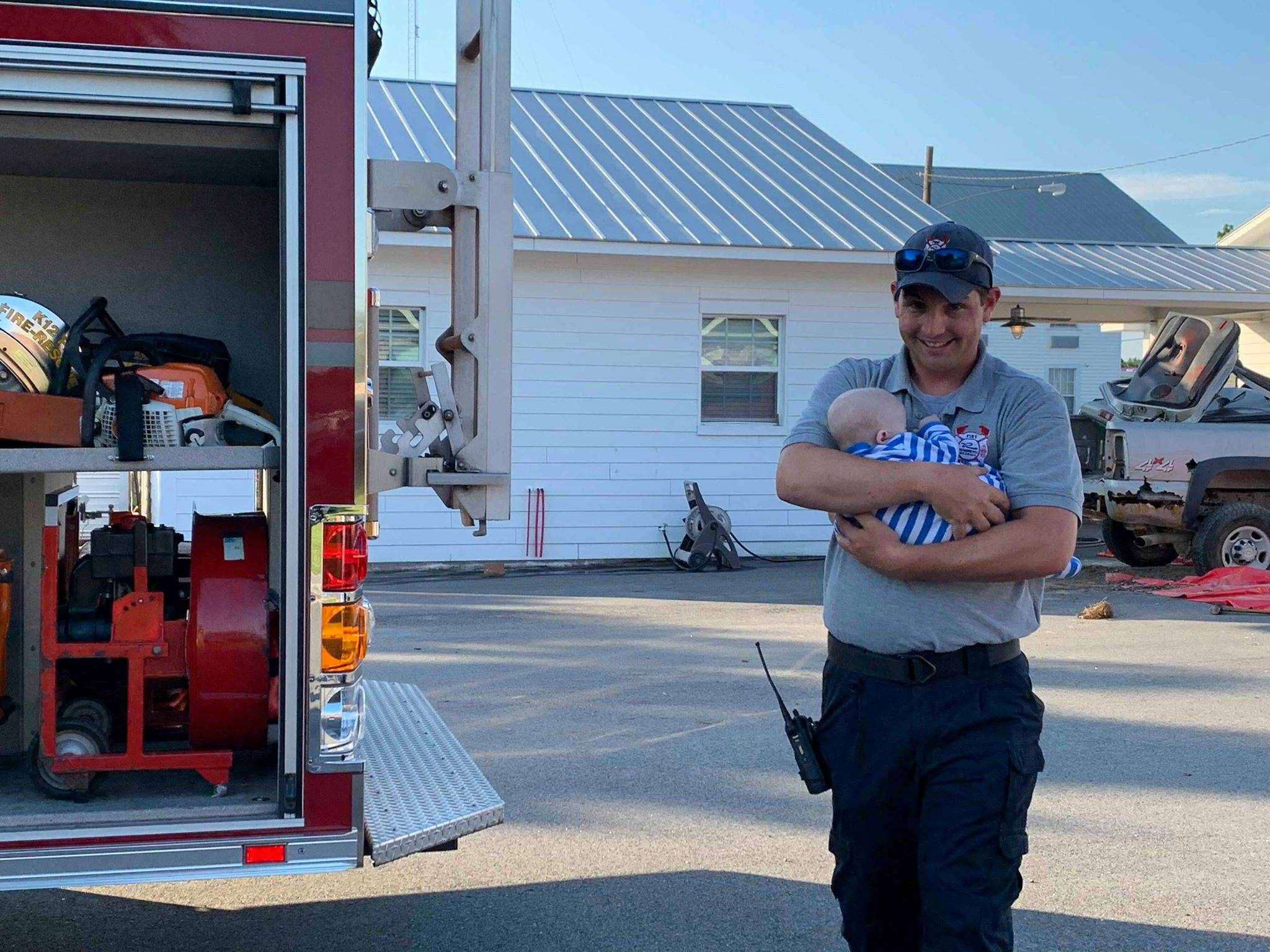 A man holds a baby next to a fire truck