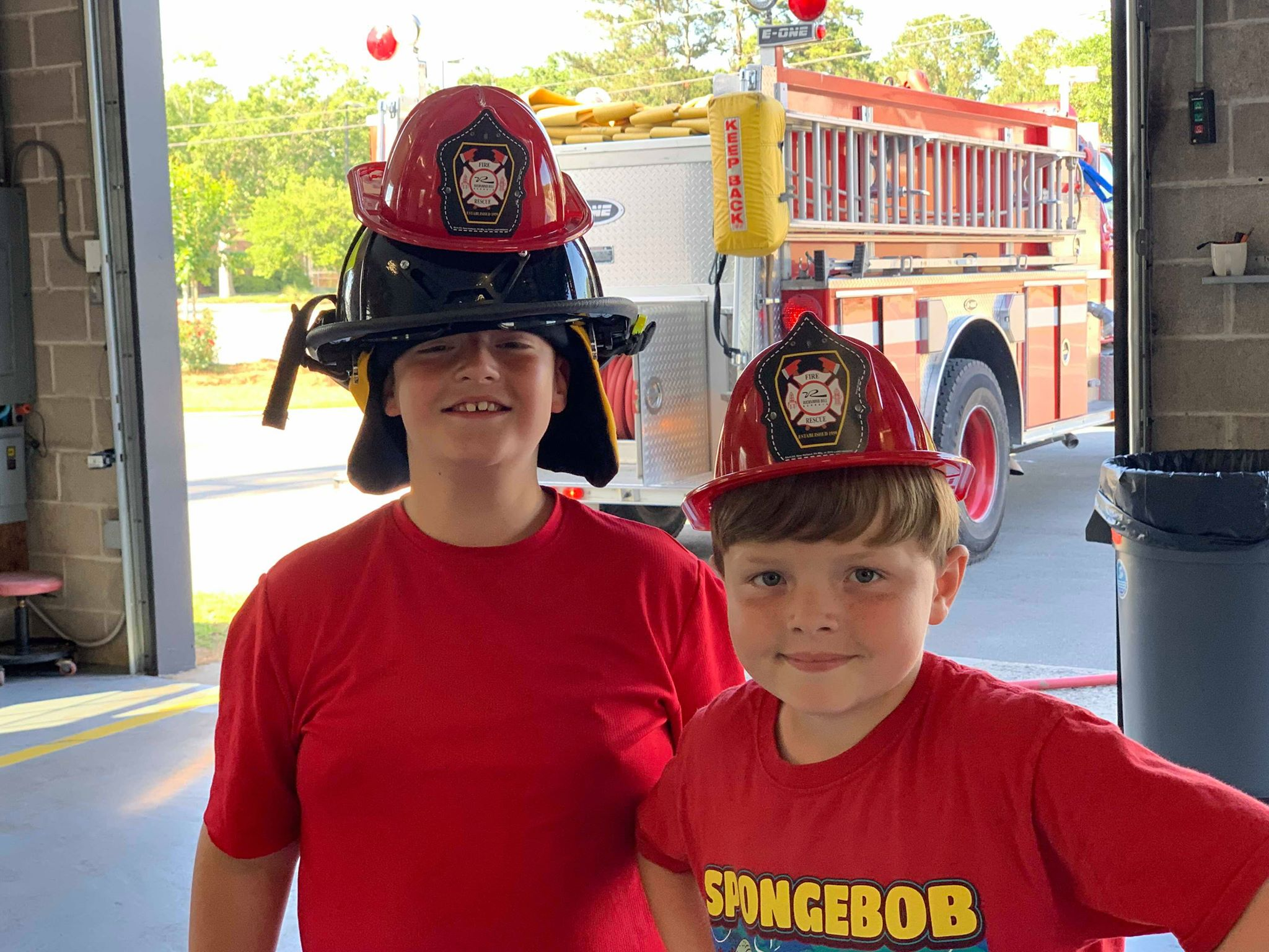Two kids wearing firefighters hats