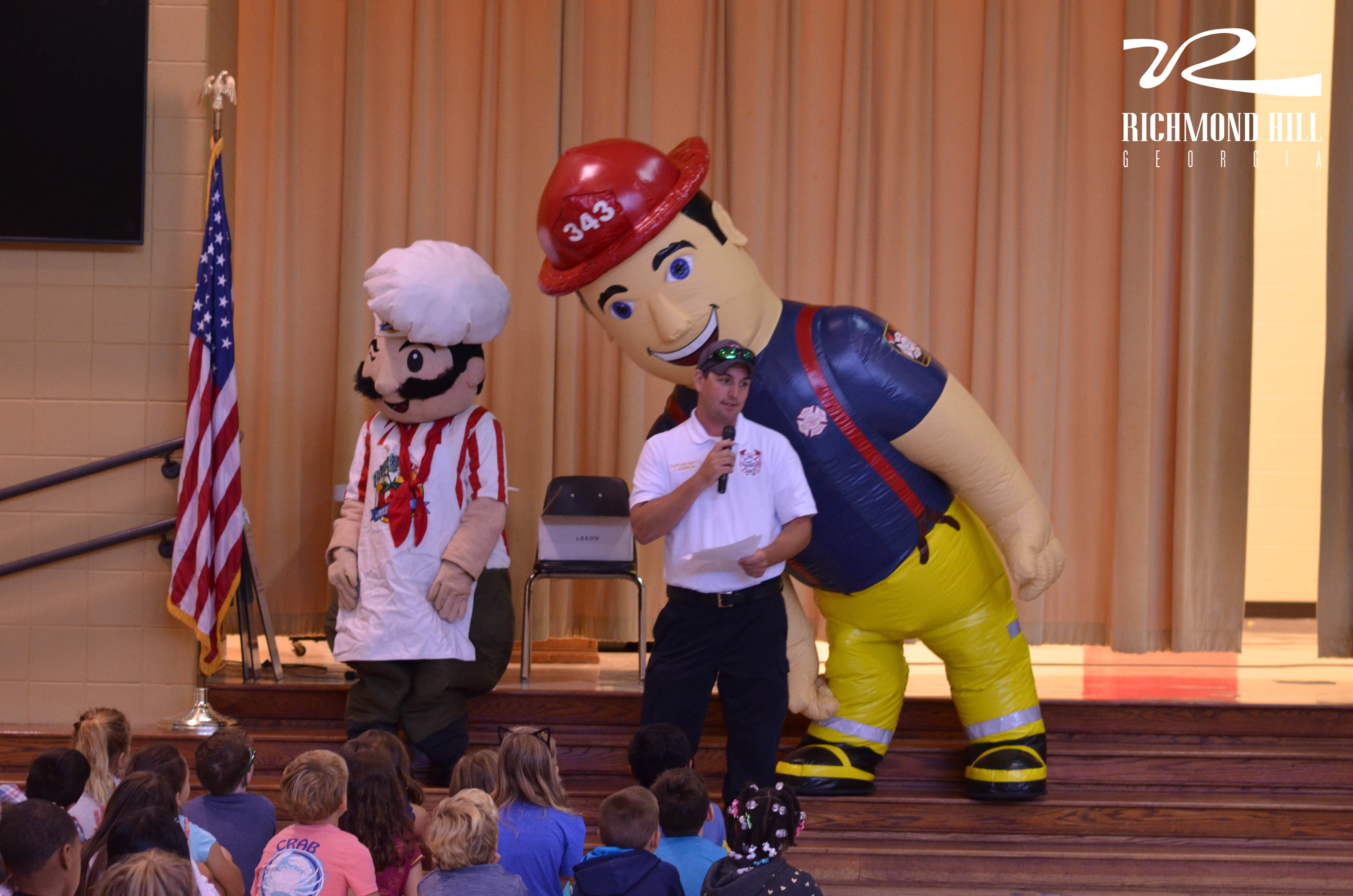 A man with a microphone stands next to a firefighter mascot and someone in a chef's suit