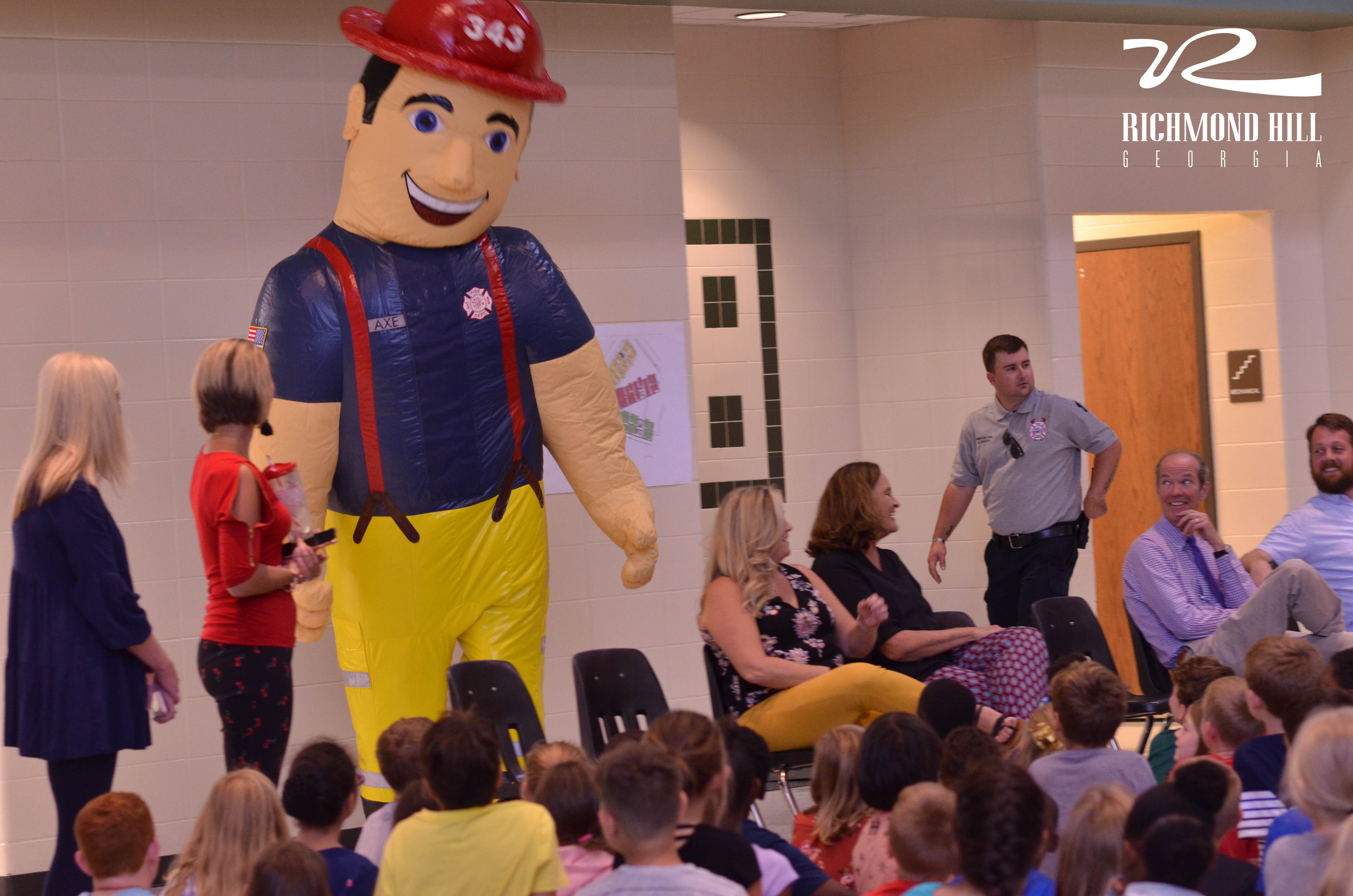 A large fire fighter mascot stands in front of a crowd