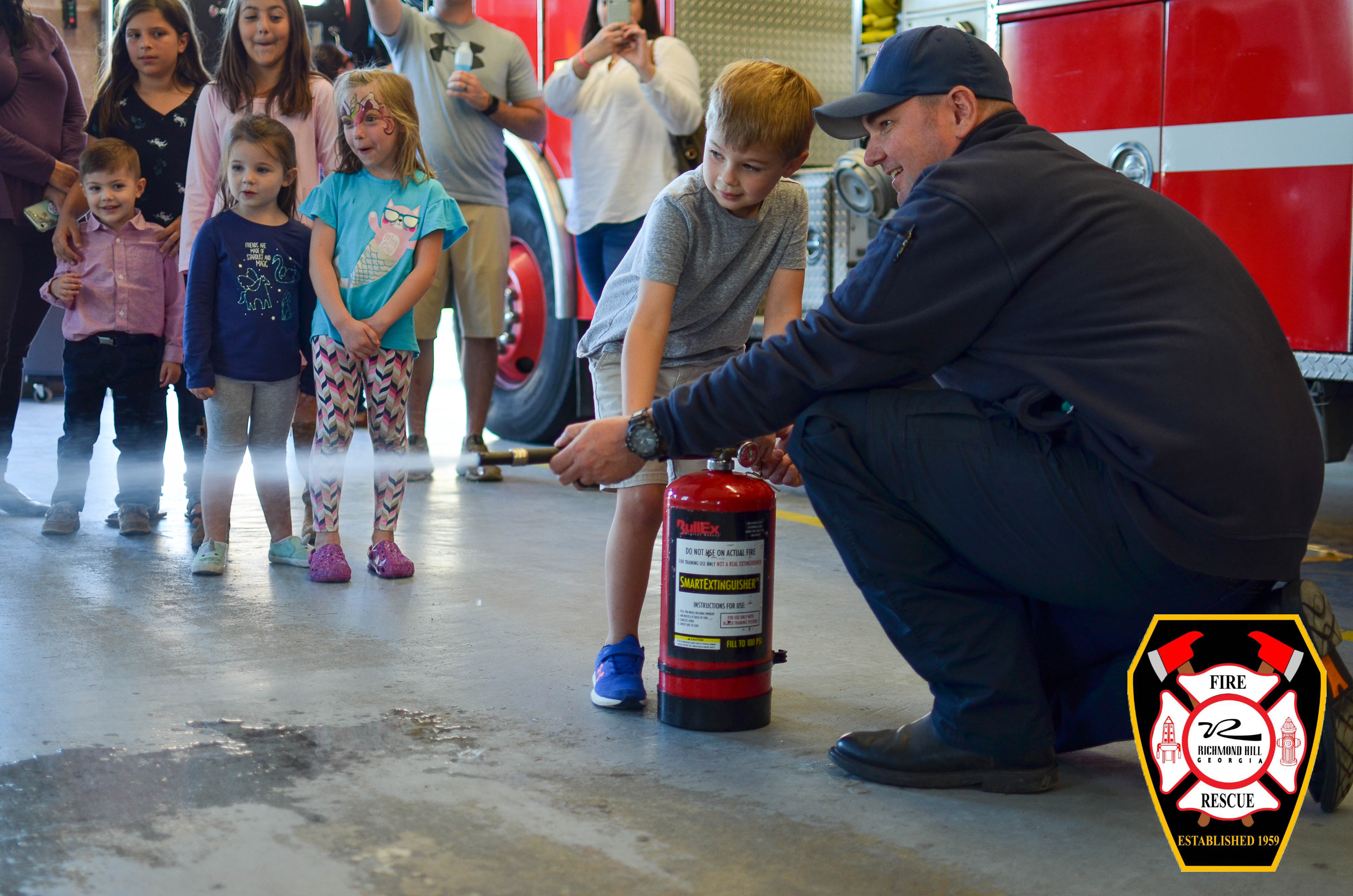 A fire fighter shows a child how to aim a fire extinguisher