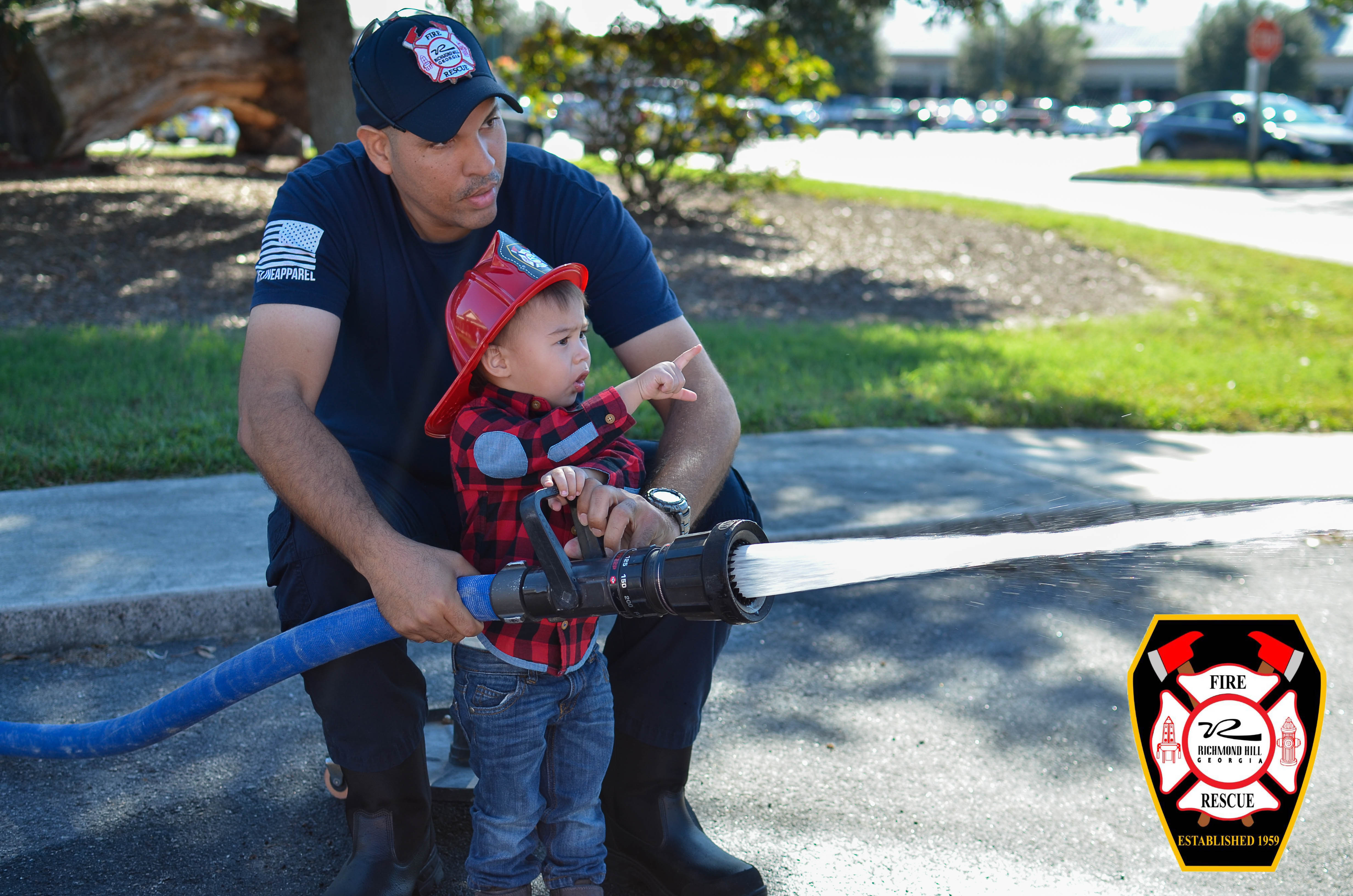 A fire fighter helps a child aim a water hose
