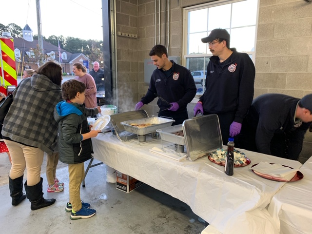 Fire Department staff serves food to a woman and child