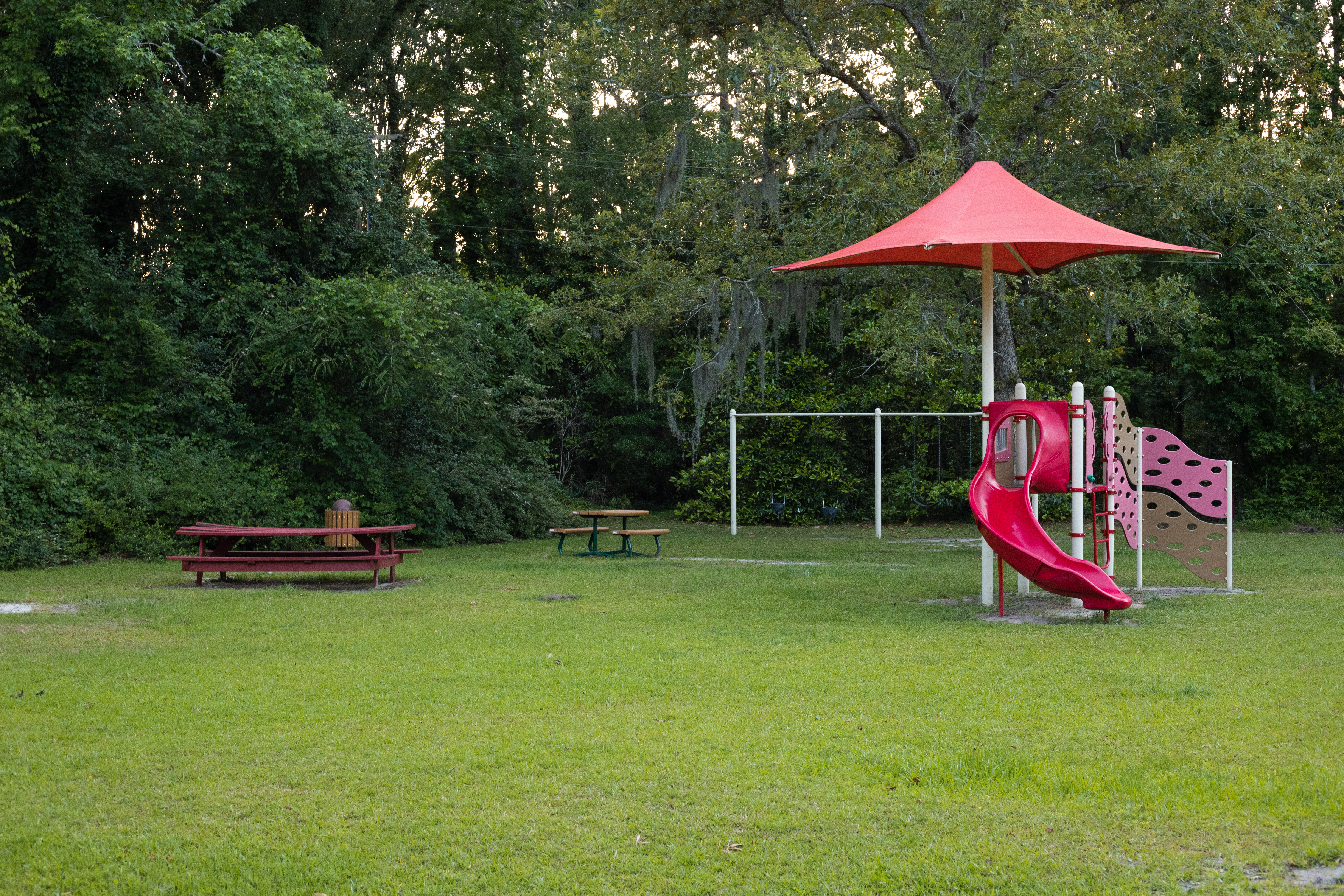 playground structure and red picnic tables