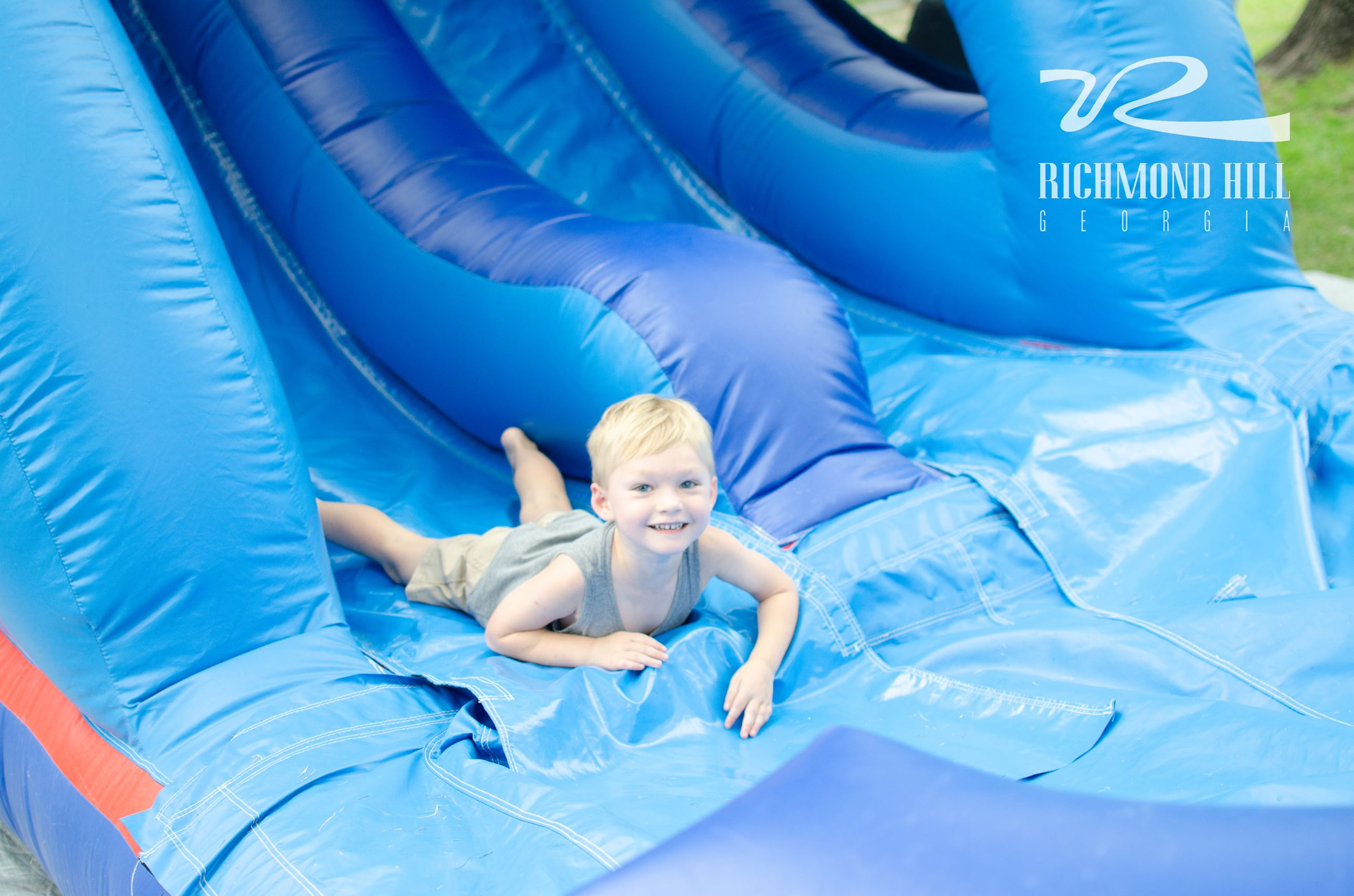 boy at the bottom of blue water slide